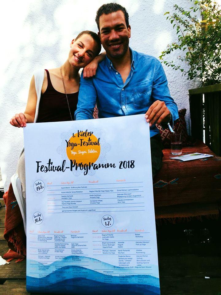 Ayla und Barak präsentieren das Programmplakat zum 1. Yogafestival in Kiel